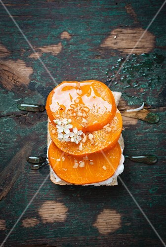 A slice of bread topped with quark, persimmons, hazelnuts and agave syrup