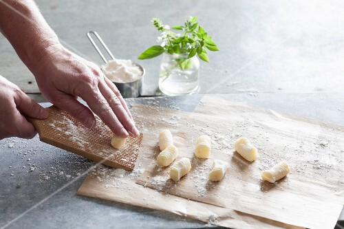 Homemade gnocchi: gnocchi being rolled on a board
