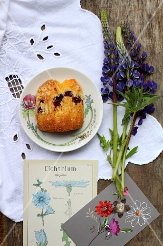 A slice of sponge cake on a plate next to flower cards and lupins