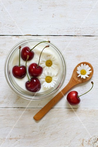 Yoghurt garnished with cherries and daisies (seen from above)