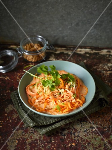 Thai coconut curry on a bed of vegetable noodles with peanuts