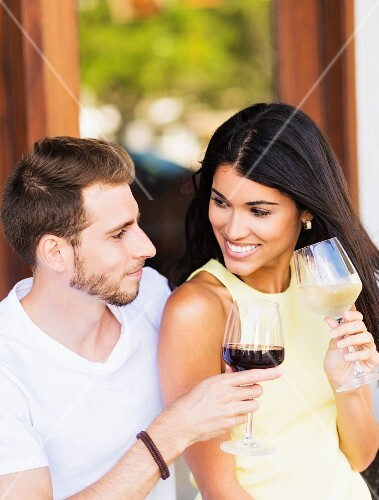 A couple on a terrace drinking wine