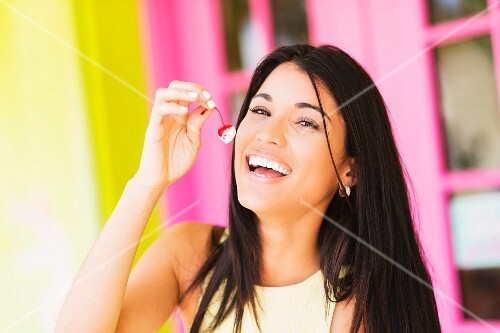 A woman eating a cherry with ice cream