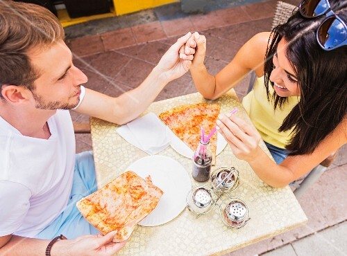 A couple eating pizza at a pavement cafe