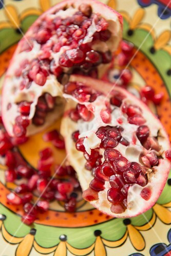 A sliced pomegranate on a colourful plate