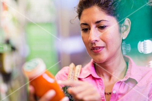 A woman in a supermarket reading a list of ingredients on a package