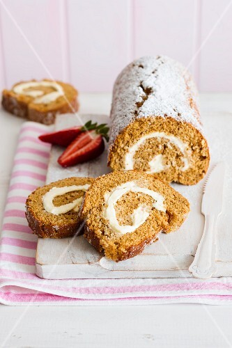 Ginger Swiss roll with icing sugar, sliced