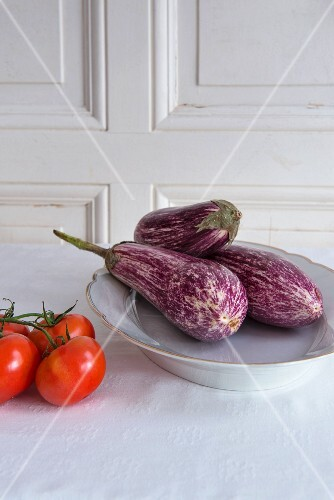 Aubergines on a porcelain plate next to tomatoes