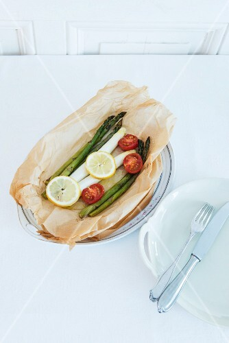 Green and white asparagus in baking paper with cocktail tomatoes and lemon