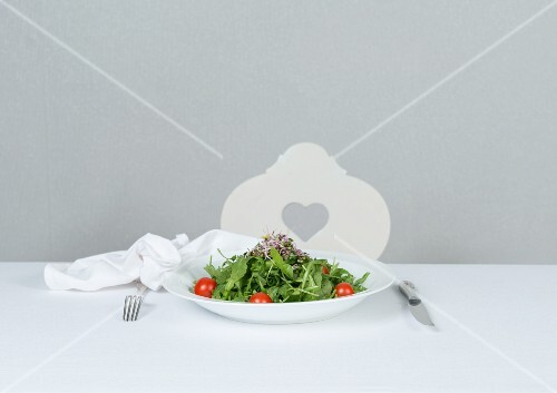 Rocket salad with cocktail tomatoes and beetroot sprouts on a porcelain plate