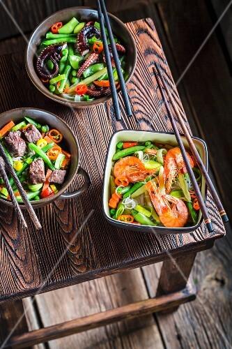 Drei Nudelgerichte mit Rindfleisch, Garnelen, Oktopus und Gemüse (Asien)