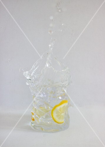 Gin and tonic splashing out of a glass against a white background