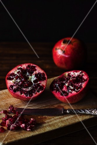 A halved pomegranate on a wooden chopping board