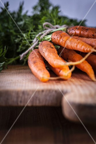 Fresh carrots on a wooden chopping board