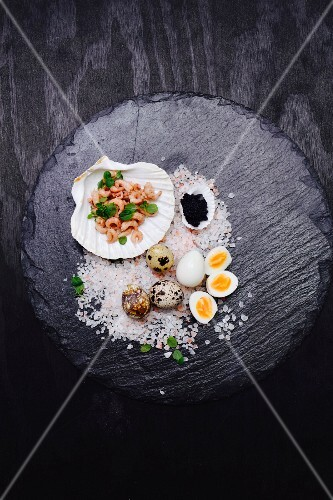 Quail's eggs, shrimps and caviar in a scallop shell