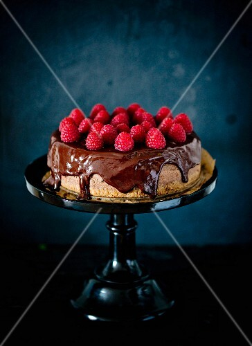 A whole chocolate cheesecake with chocolate glaze and raspberries