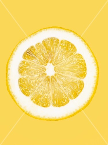 A slice of lemon on a yellow surface, close-up