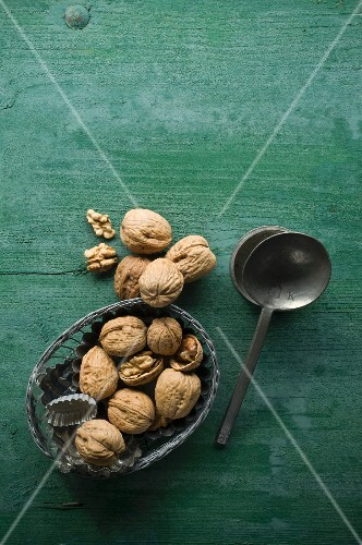 Walnuts, shelled and unshelled, in a bowl on a rustic wooden surface next to a spoon