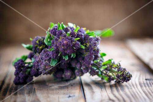 Purple sprouting broccoli on a wooden board