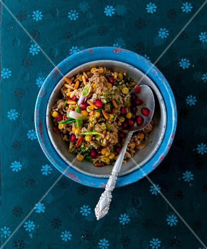 Oriental rice salad with pomegranate seeds and pine nuts