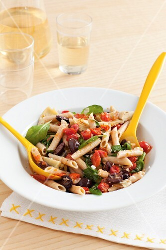 Wholemeal penne pasta with artichoke hearts, rocket, grape tomatoes and olives
