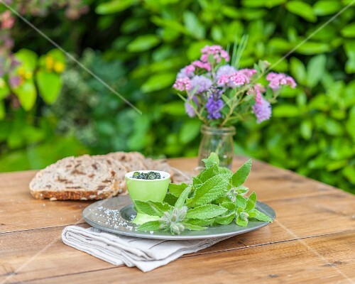 Borage, slices of bread and a vase of flowers on a garden table