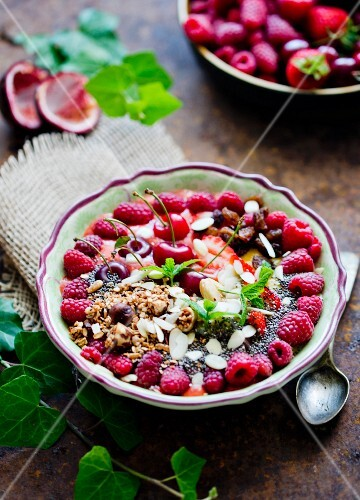 A smoothiey bowl with cherries and raspberries
