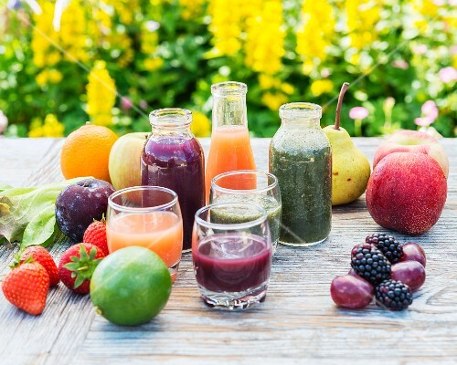 Various smoothies in glasses and bottles with fruit and salad