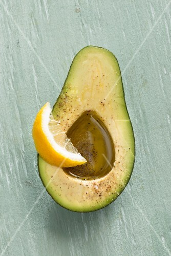 An avocado with olive oil and lemon