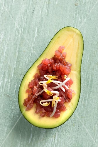 Avocado filled with tuna fish tartare and bean sprouts