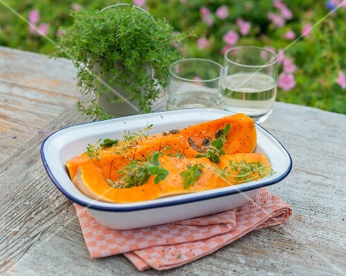Quartered butternut squash with oil and herbs in a baking dish