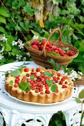 Summer tart with vanilla cream, raspberries and wild strawberries