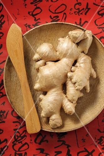 Fresh ginger roots on a wooden plate