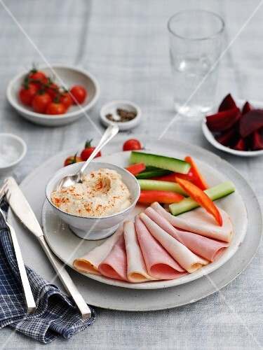 Meat platter with vegetable sticks and houmous
