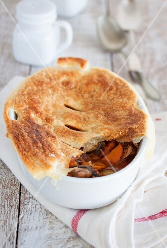 Chicken pot pie with vegetables and a puff pastry lid
