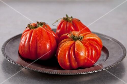 Three beefsteak tomatoes on a metal plate