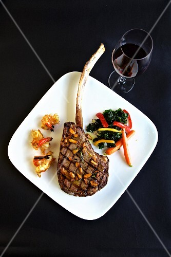 Grilled tomahawk steak with sides and a glass of red wine (seen from above)