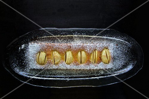 Apple loaf cake on a black surface (seen from above)