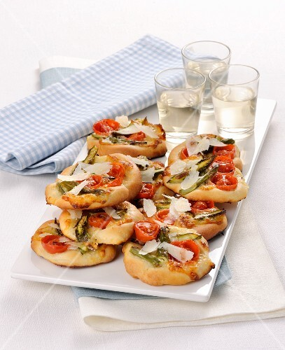 Mini pizzas with green asparagus and cherry tomatoes