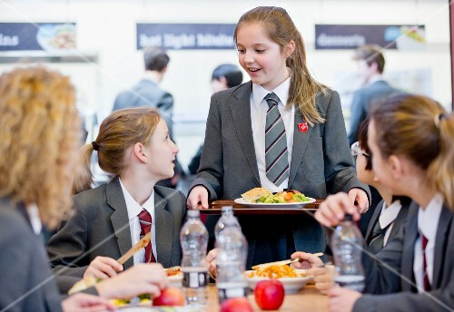 Middle school pupils eating lunch and talking in the school cafeteria
