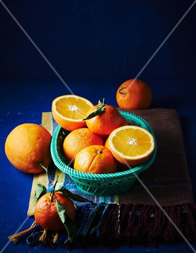 Oranges, whole and halved, in a basket and next to it