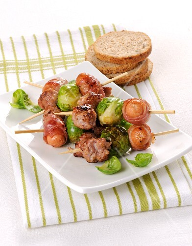 Sausages wrapped in bacon and Brussels sprouts on skewers