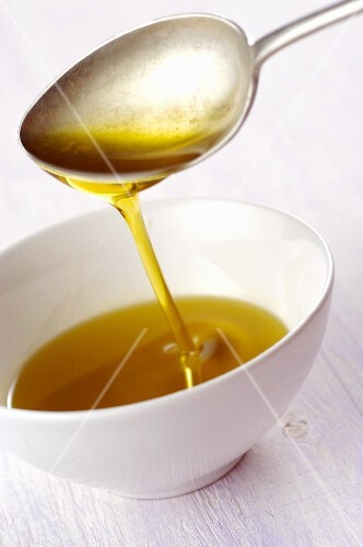 Olive oil flowing from a spoon into a bowl