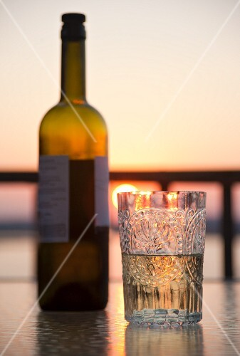 White wine in a crystal glass at sunset