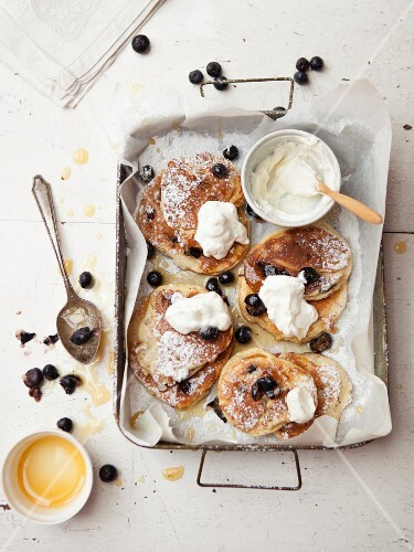 Pancakes with blueberries and cream on a baking tray
