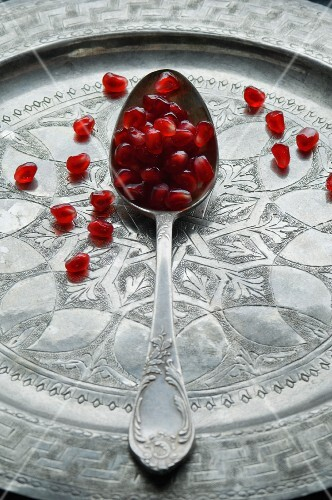 Pomegranate seeds on spoon