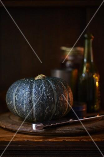 A green pumpkin on a wooden plate