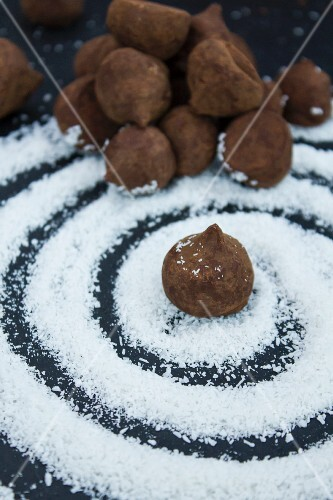 Chocolate truffles on a swirl of grated coconut