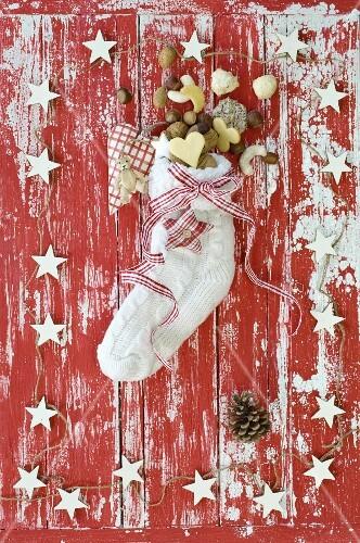 Nikolausstrumpf gefüllt mit Nüssen und Plätzchen auf rot-weißem Holzuntergrund