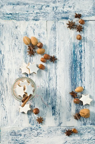 Cinnamon stars, cinnamon sticks, star anise and nuts on a wooden surface (seen from above)